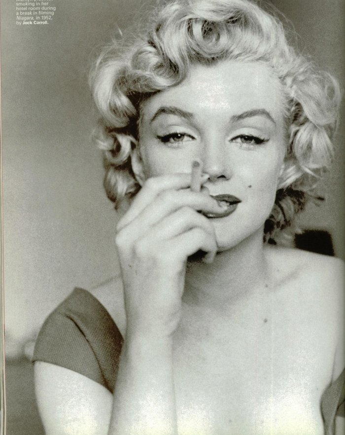 "Marilyn is relaxing in her hotel room with a cigarette. Shot by Jock Carroll during the filming of ""Niagara"" in 1952"